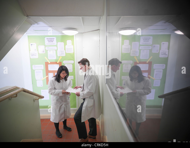 Science teacher discussing coursework with student - Stock Image