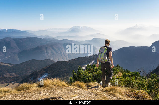 Man walking hiking on mountain trail. Great view. - Stock Image