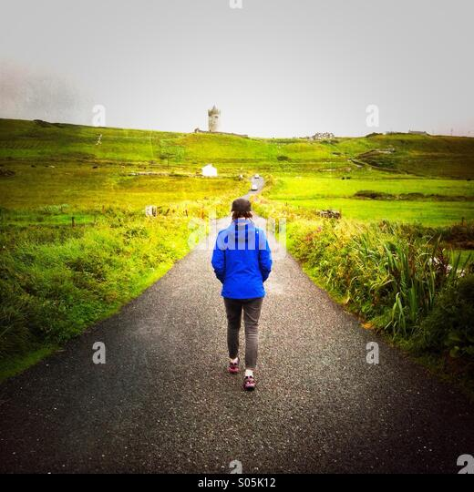A female walks up a road. Doolin, co. Clare, Ireland. - Stock-Bilder