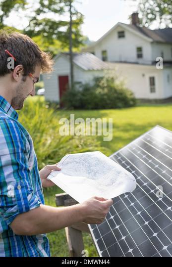 A man using a plan to place a solar panel in a farmhouse garden. - Stock Image