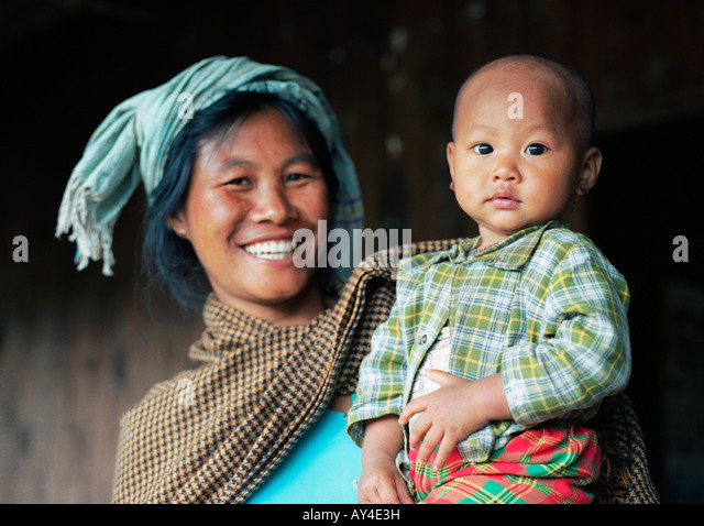 A woman of the Danu tribe is holding her baby on her arms - Stock-Bilder