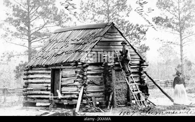 Full length standing portrait of African American man and woman in front of log cabin, male wearing light jacket, - Stock Image