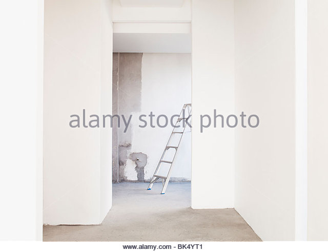 Ladder and freshly painted walls in empty house - Stock Image