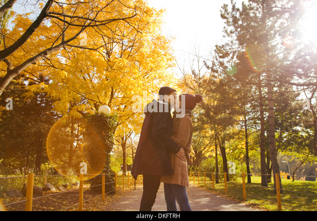 Young couple kissing in autumn park, Vienna, Austria - Stock Image