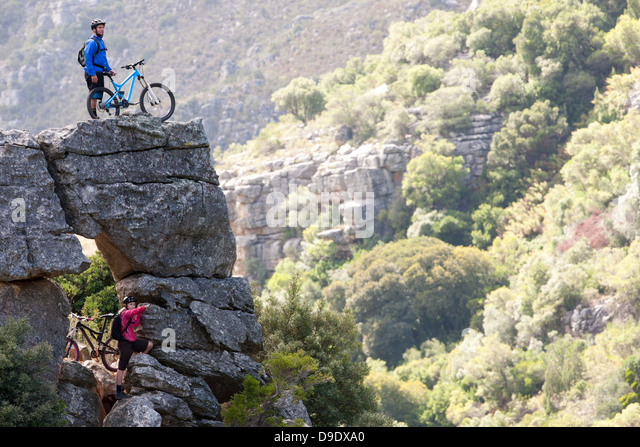 Mountain biking couple on rock formation looking ahead - Stock Image