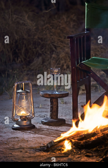 Relaxing at a campfire with a glass of red wine Jack's Camp  Makgadikgadi Pans, Botswana - Stock Image