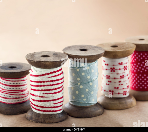 Wooden ribbon spools for Christmas present wrapping on brown vintage background - Stock-Bilder