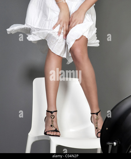 woman legs on a white chair - Stock Image