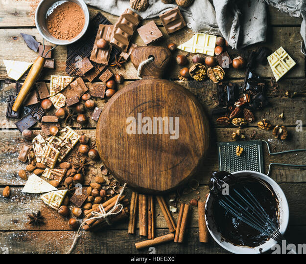 Pieces of white, dark and milk chocolate, nuts, cocoa powder, melted chocolate and spices with wooden board in center. - Stock Image