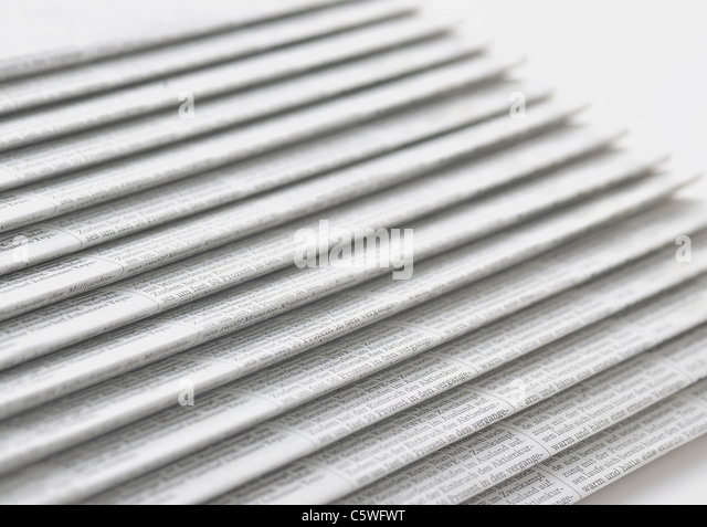 Row of newspapers on white background - Stock Image