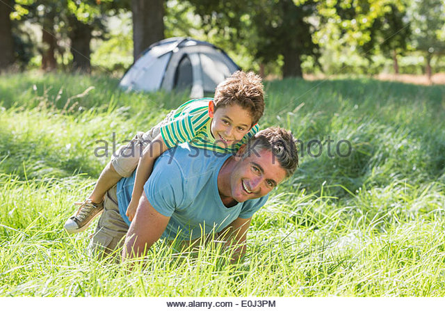 Father And Son Having Fun On Camping Trip In Countryside - Stock Image