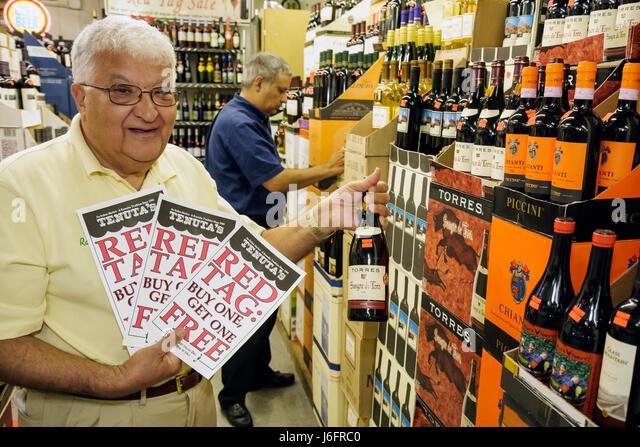 Wisconsin Kenosha Tenuta's Delicatessen Liquors and Wines Italian market owner man senior red wine bottle imported - Stock Image