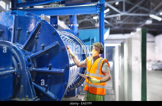 Worker checking metal ore grinding mill - Stock-Bilder