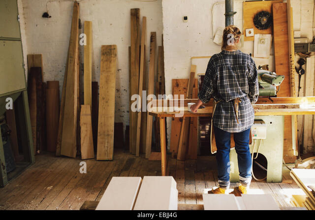 Young craftswoman at workbench in pipe organ workshop - Stock Image