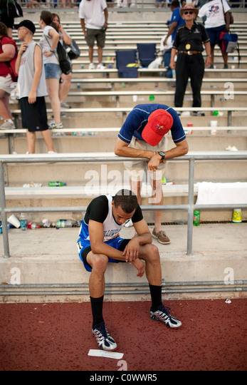 Father talks to his downcast son after disappointing finish in race at the Texas state high school track championships - Stock Image