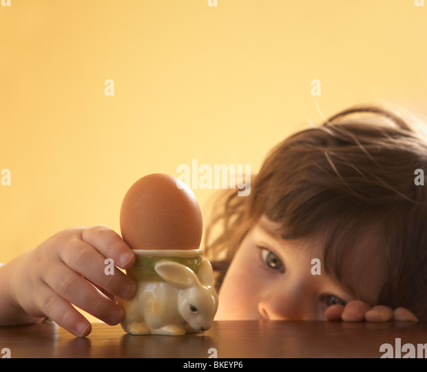 Young child focusing on bunny egg holder - Stock Image