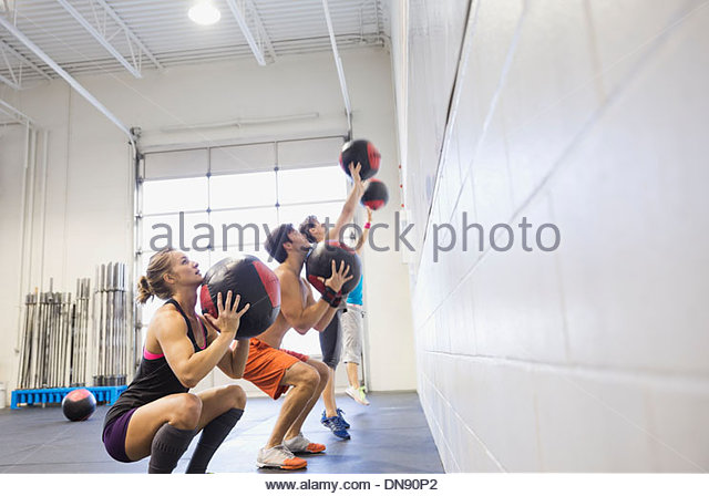 People practicing medicine ball wall throws - Stock Image