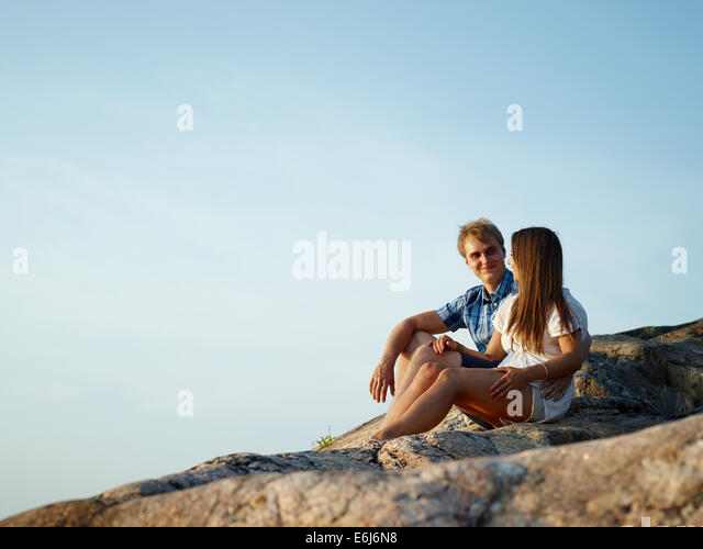 Young couple sits together on the cliff, blue sky on background - Stock-Bilder
