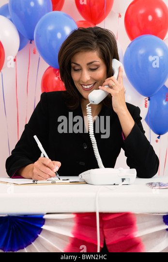 USA, Illinois, Metamora, Smiling woman talking on phone, red and blue balloons in background - Stock Image