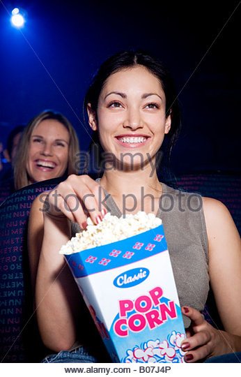 Woman watching a humorous film at the cinema, laughing and eating popcorn - Stock-Bilder