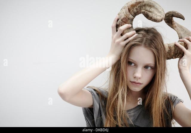 Portrait of girl holding horns on her head - Stock Image