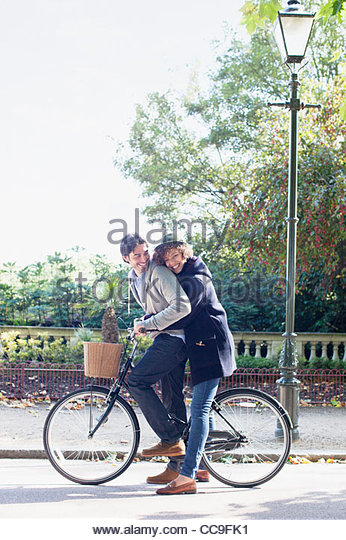 Couple riding bicycle in park - Stock Image