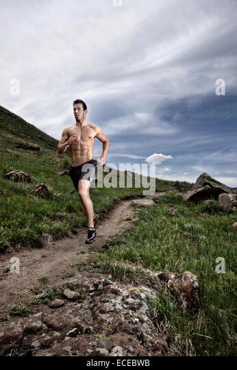 USA, Colorado, Jeferson County, Golden, Shirtless man running long hillside footpath - Stock Image