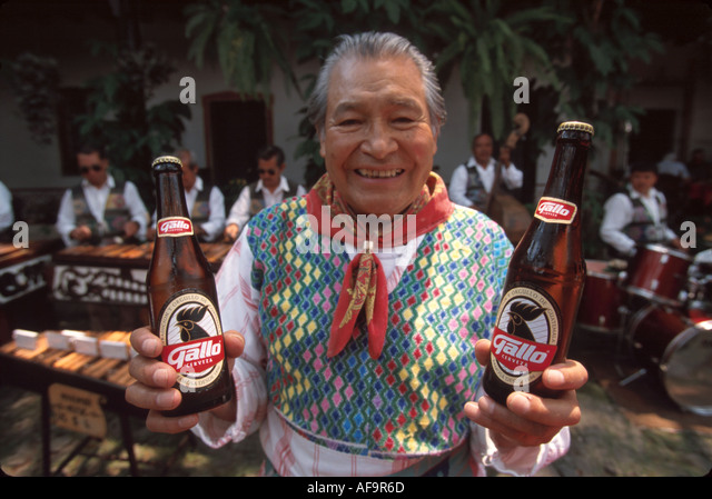 Guatemala La Antigua colonial capitol until earthquake waiter offers local bottled beer - Stock Image