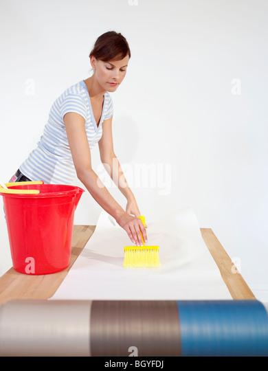 Woman brushing paste onto wallpaper - Stock Image