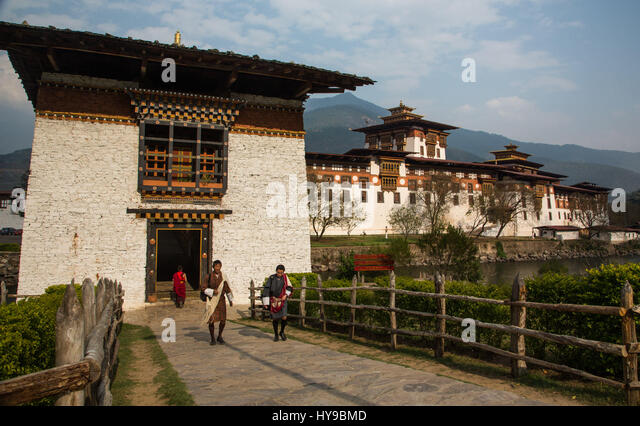Bhutanese men in traditional ghos at the bridge gate house and the Punakha Dzong.  Punakha, Bhutan. - Stock Image