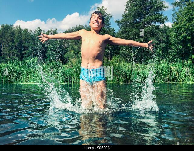 Young boy splashing in the river - Stock Image