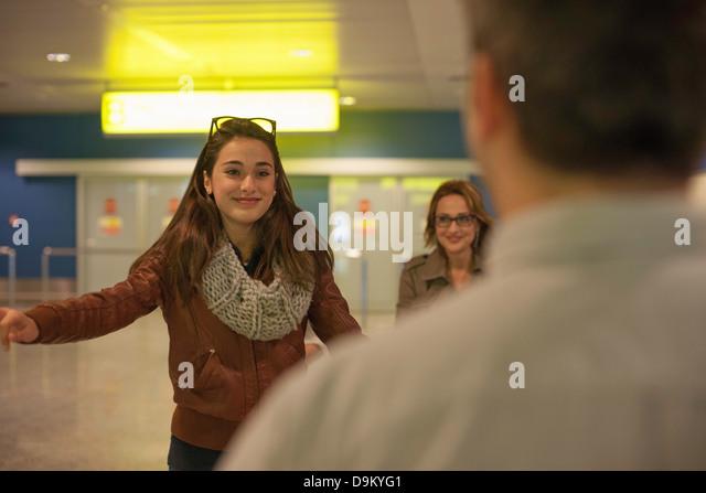 Teenage girl arriving in airport, man in foreground - Stock-Bilder