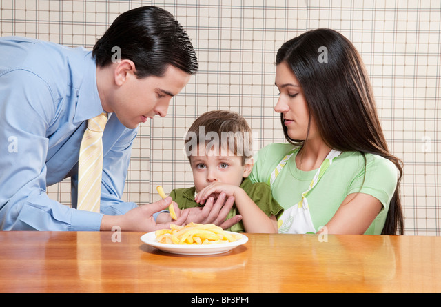 Man feeding French fries to his son - Stock Image