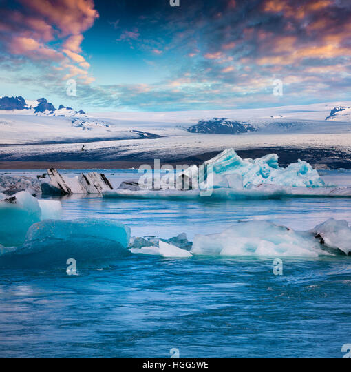 Floating of blue icebergs in Jokulsarlon glacial lagoon. Colorful sunset in Vatnajokull National Park, southeast - Stock Image