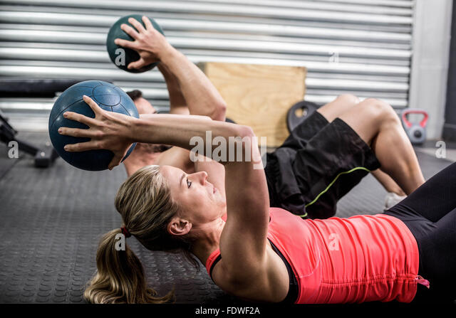 Fit couple doing abdominal ball exercise - Stock Image