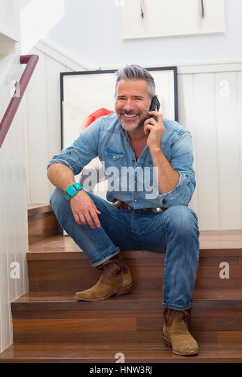 Caucasian man sitting on staircase talking on cell phone - Stock-Bilder