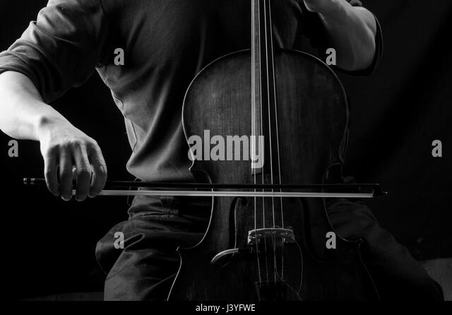 Black and white photograph of a man in playing cello with a bow, his face hidden - Stock Image