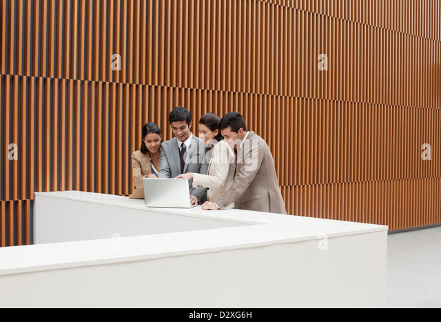 Business people using laptop at ledge in office - Stock Image