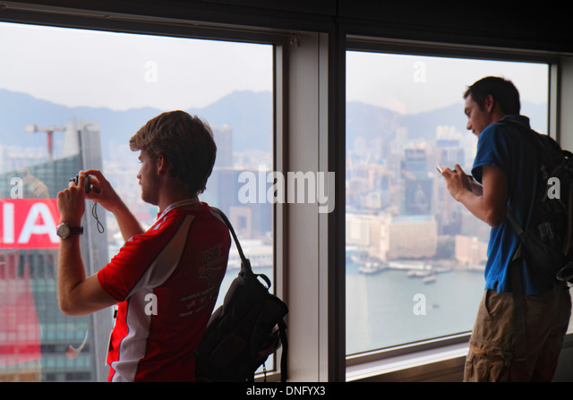 China Hong Kong Island Central Bank of China Tower observation deck observatory man taking picture Victoria Harbour - Stock Image