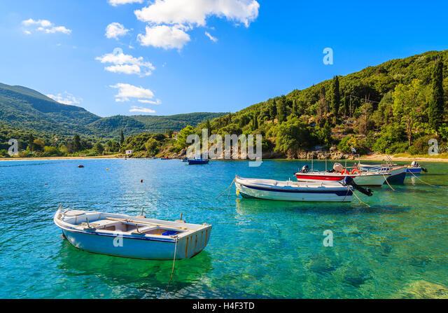 Greek fishing boats on turquoise sea water in beautiful bay, Kefalonia island, Greece - Stock Image