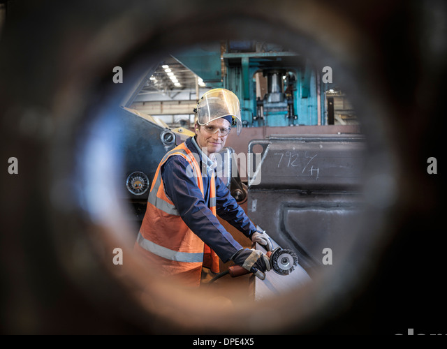 Engineer portrait in factory viewed through hole in steel - Stock Image