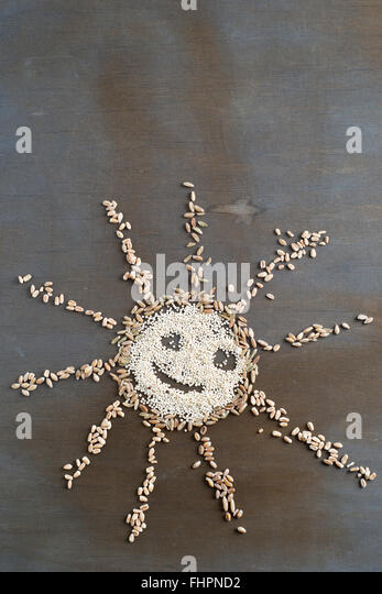 Different grains building a smiling sun - Stock Image