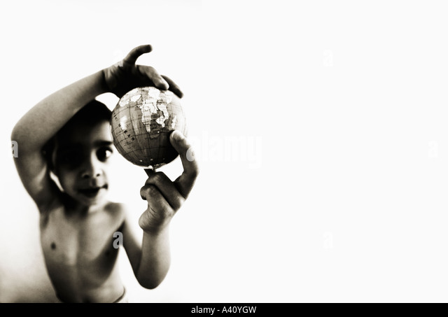 Boy holds globe in hand - Stock Image