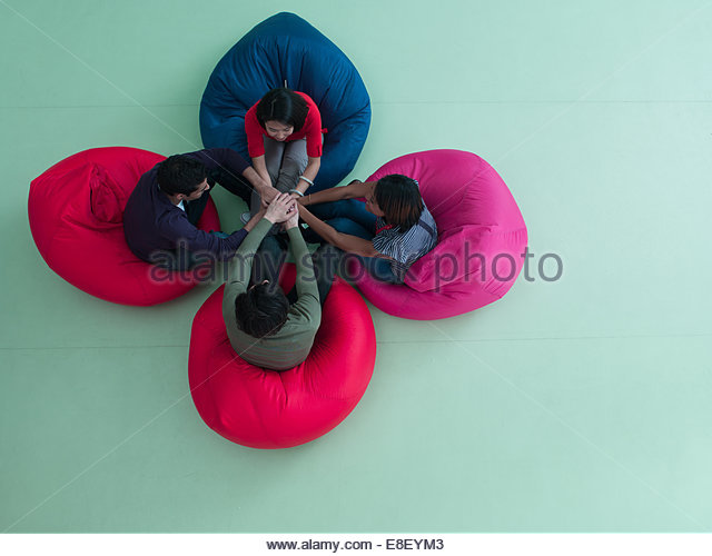 Smiling business people sitting in bean bag chairs with stacked hands - Stock-Bilder