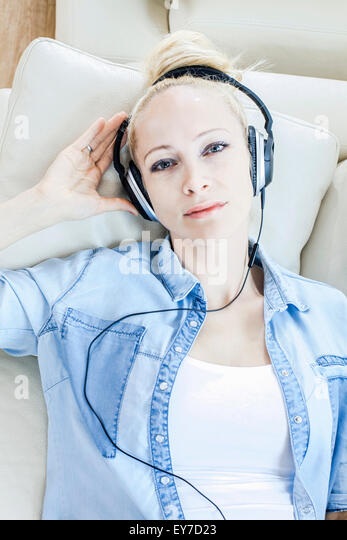 Blond woman listening to music with headphones - Stock Image