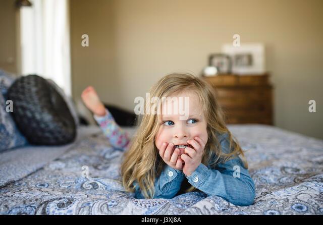 Girl lying on bed looking sideways - Stock Image