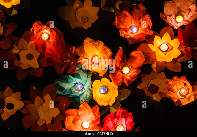 Paper lotus flowers with candles float on a river at night to mark the Chinese Mid-Autumn Festival - Stock-Bilder