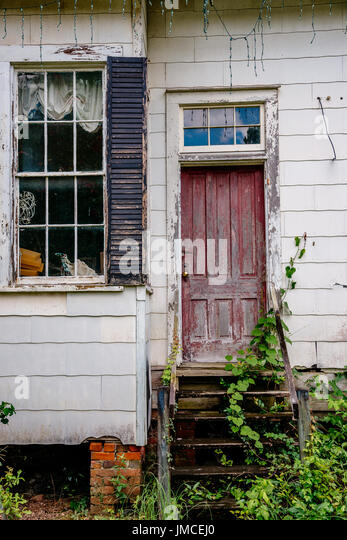 Entrance to a long since abandoned building that once had a bright red door. - Stock Image
