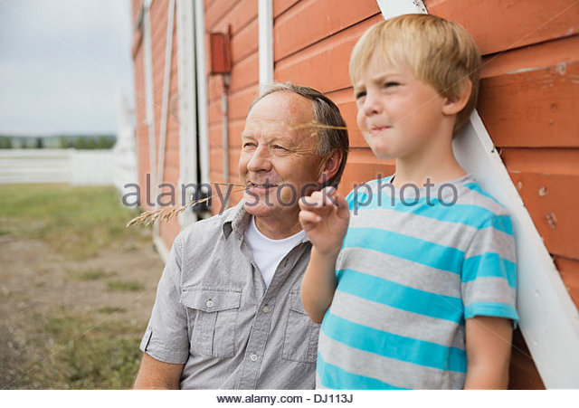 Grandfather and grandson relaxing outdoors - Stock Image