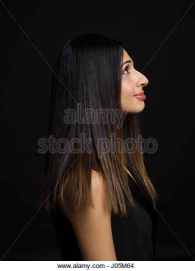 Profile portrait Indian woman looking up against black background - Stock Image